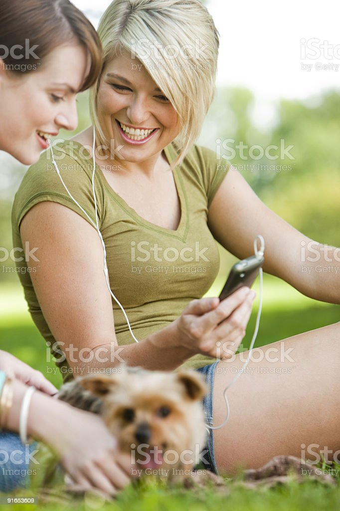 Women listening to music at park royalty-free stock photo