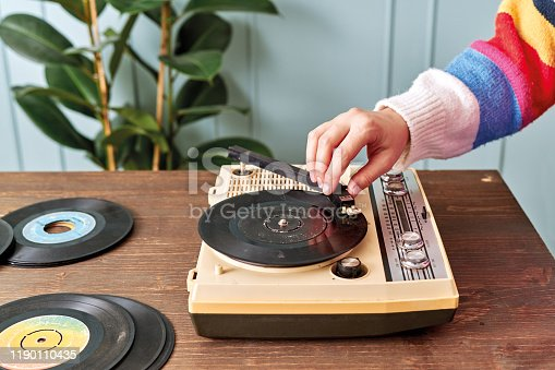 Women listening to music with retro turntable on table