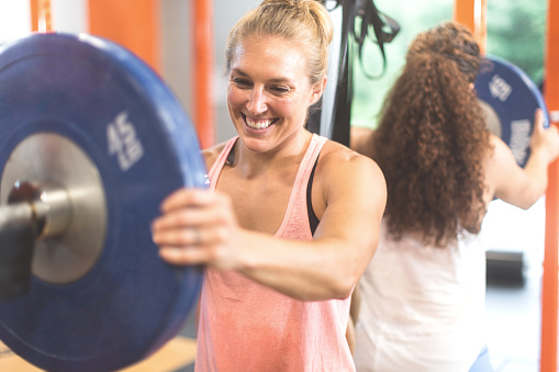 istock Women loading a barbell for weightlifting cross training workout 598078420