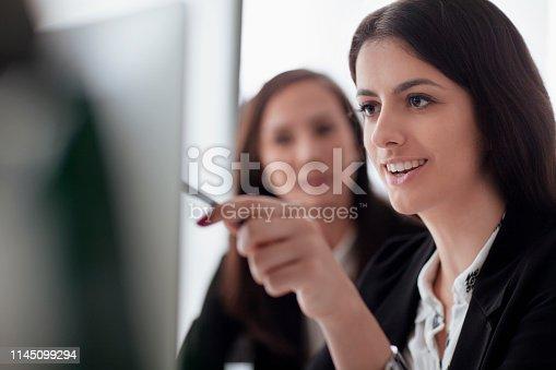 istock Women looking at computer screen in office 1145099294
