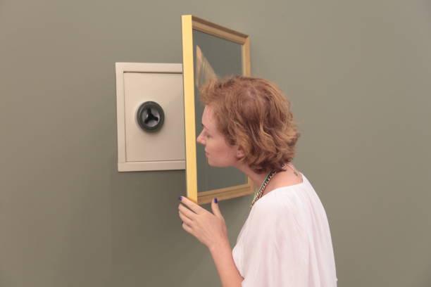 Women looking at hidden safe. - foto stock