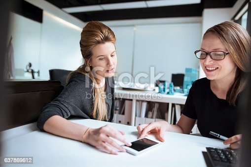 istock Women looking at ideas on smart phone together in office 637869612