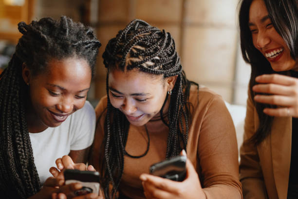 Women looking at phone using Internet dating app stock photo