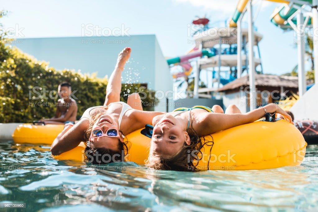 Frauen, die in die Kamera schaut auf Floaties im Schwimmbad – Foto