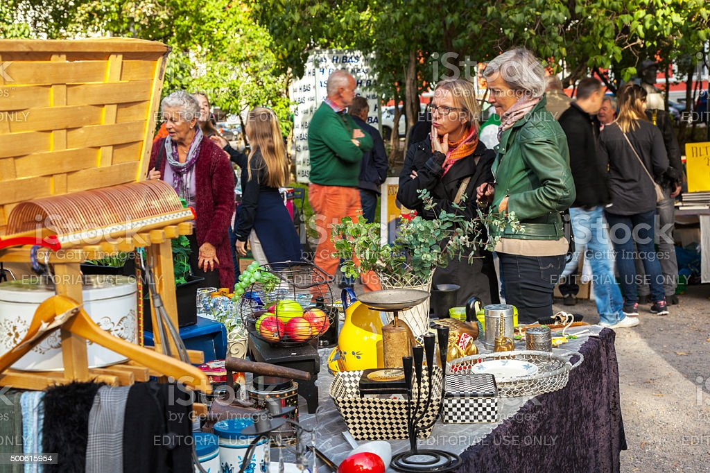 Women looking at used items  on outdoor market. stock photo