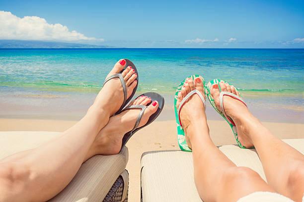 frauen entspannen und sonnenbaden auf einem idyllischen strand - salzwasser sandalen stock-fotos und bilder