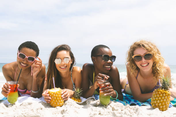 Women lying at beach while having pineapple juice stock photo
