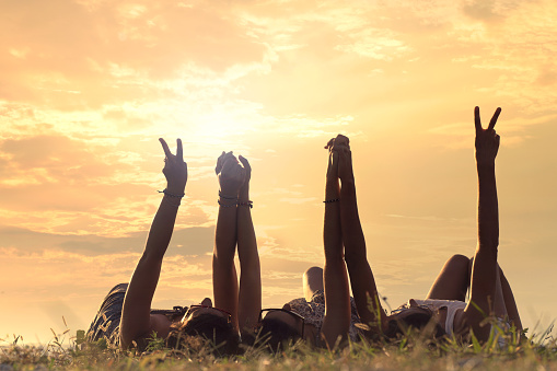 istock women lying in the meadow raise their arms 610846798