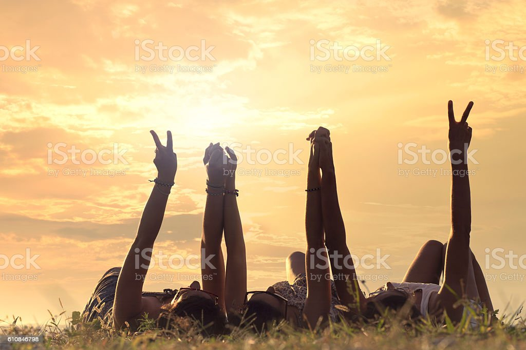 women lying in the meadow raise their arms stock photo