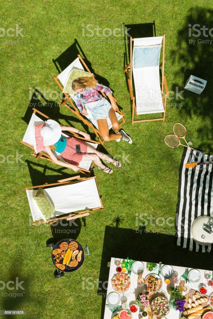 Women lying on deckchairs stock photo