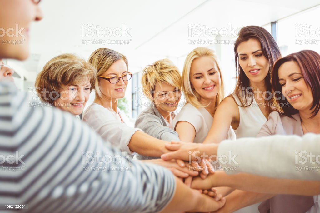 Women making a pile of hands Group of women making a pile of hands during a training session. Female stacking their hands together. A Helping Hand Stock Photo