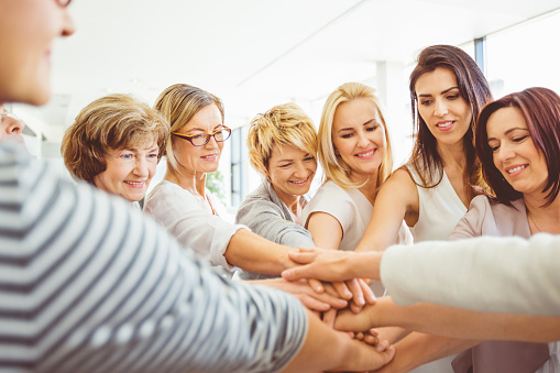Women Making A Pile Of Hands Stock Photo - Download Image Now