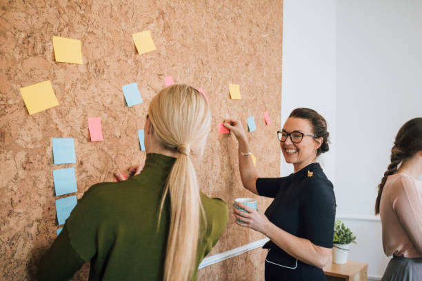 Women Making Business Notes Two women are at work in an office. They are standing at a cork board and are having a discussion as they pin things up. passion stock pictures, royalty-free photos & images