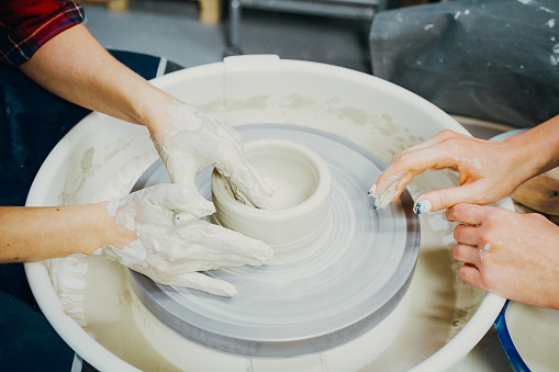 Women making ceramic pottery, concept for workshop and master class, four hands close-up, focus on potters, palms with pottery. Creative hobby concept. Earn extra money, side hustle