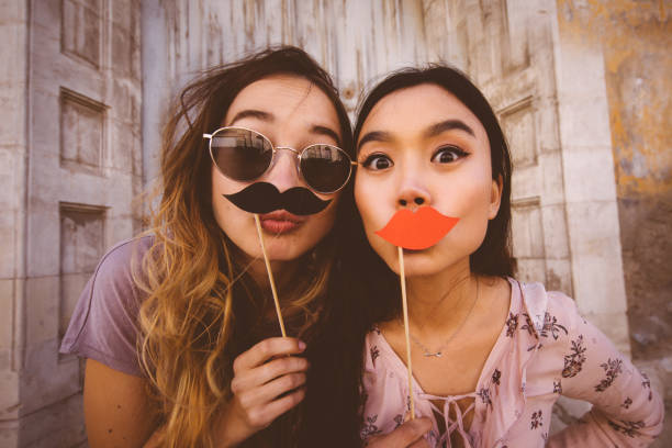Women making faces with mustaches and lips on a stick stock photo