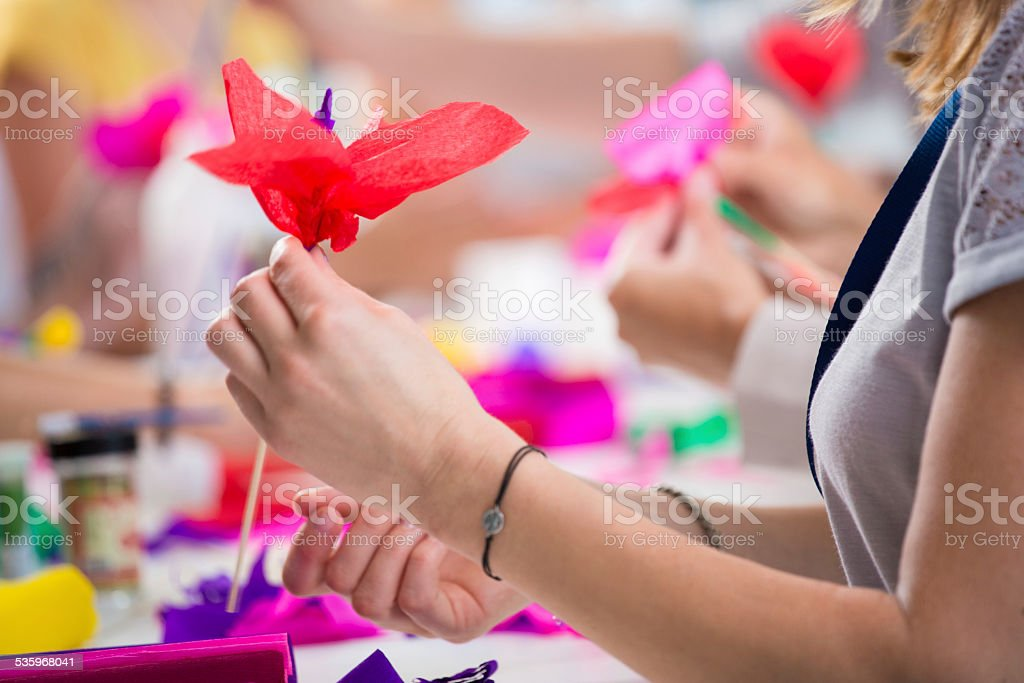 Women making paper flowers Group of women working on workshop, making coloful paper flowers. Close up of hand holding flower. Unrecognizable person. 2015 Stock Photo