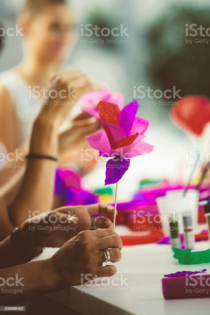Women making paper flowers Group of women working on workshop, making coloful paper flowers. Close up of hands holding flower. Unrecognizable person. 2015 Stock Photo