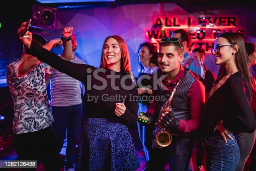 Two young beautiful women making selfie with handsome male saxophonist playing at club party. Using laser lights for show.