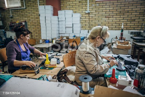Mature female shoemakers in uniforms working at shoe factory.
