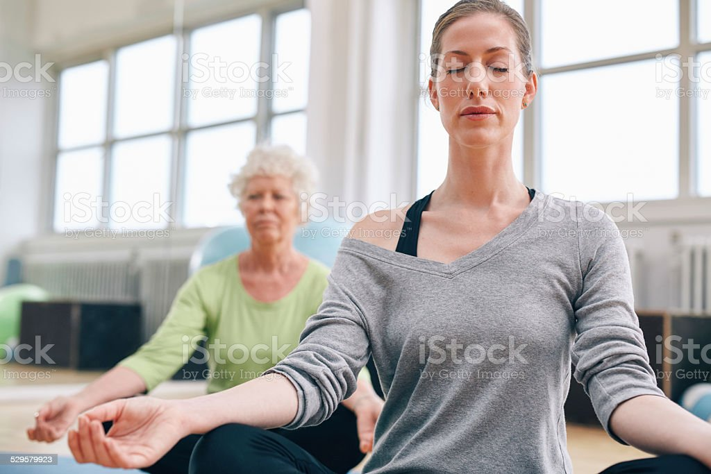 Mature woman doing yoga with senior female in background. Women...