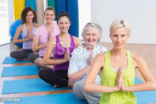 istock Women meditating with hands joined during fitness class 472537808
