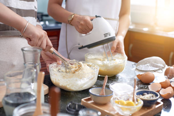 Women Mixing Cookie Dough Unrecognizable women making cookie dough in kitchen, using whisk and modern electric mixer while beating eggs electric mixer stock pictures, royalty-free photos & images