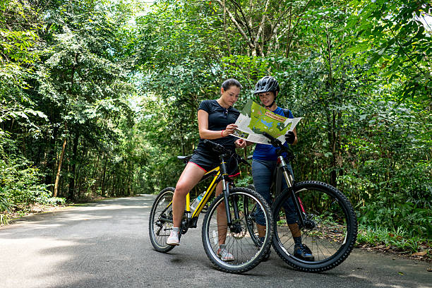 women mountain biking holding a map - singapore nature stock photos and pictures