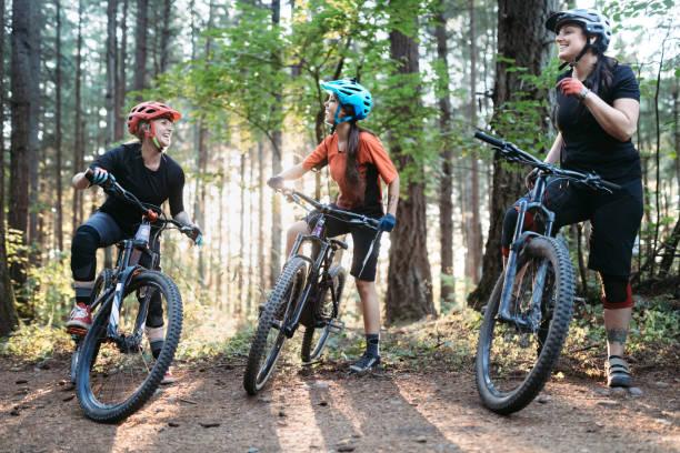 women mountain biking team - mountain biking stock photos and pictures