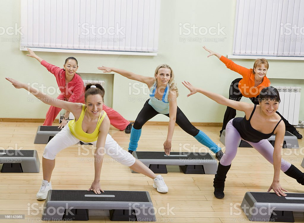Women of Different Age Doing Step Aerobics in the Gym. stock photo