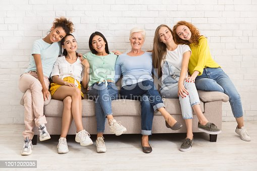 1094812112 istock photo Women Of Different Age Sitting On Sofa Smiling Indoor 1201202035