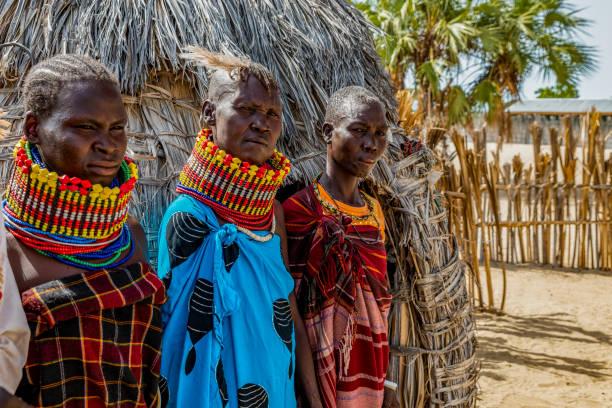 Women of the Turkana tribe, standing outside the ekol, the daytime hut. stock photo