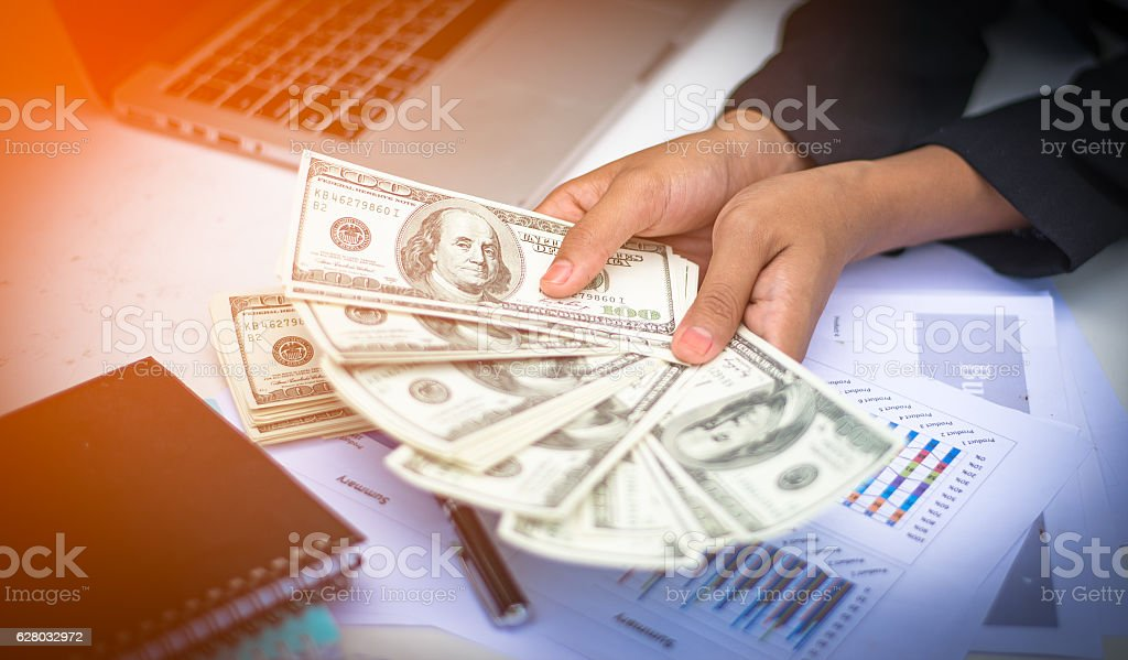 Women offering batch of hundred dollar bills stock photo