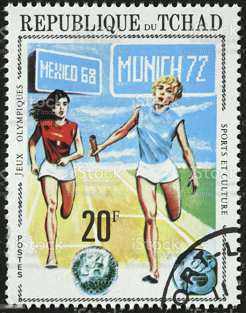 women Olympic relay sprinters on a Republic of Chad stamp stock photo