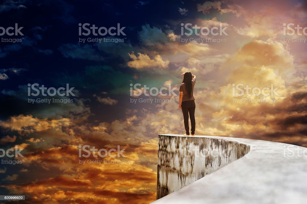 Women on dead end way high up on vast sky stock photo