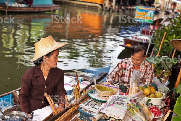 Women on her boats with the goods for sale at Damnoen Saduak Floating Market