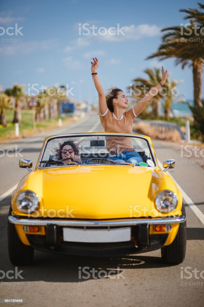Women on holidays driving convertible car on tropical island highway royalty-free stock photo