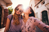 Young female teen best friends having fun walking around an antique city in Spain