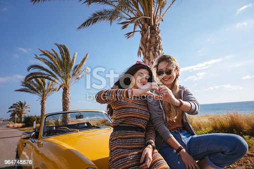 Women on road trip with convertible car making heart shape with their hands at seaside