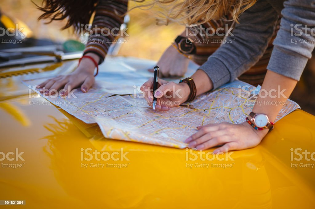 Women on summer road trip reading map for directions royalty-free stock photo