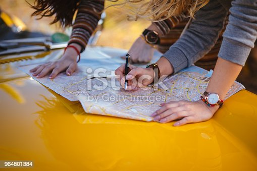 Close-up of women with retro car reading road map and making decisions about route