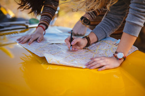 Women on summer road trip reading map for directions Close-up of women with retro car reading road map and making decisions about route road trip stock pictures, royalty-free photos & images