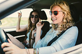 Women on the road trip. Driving in the car, singing and enjoying the journey.
