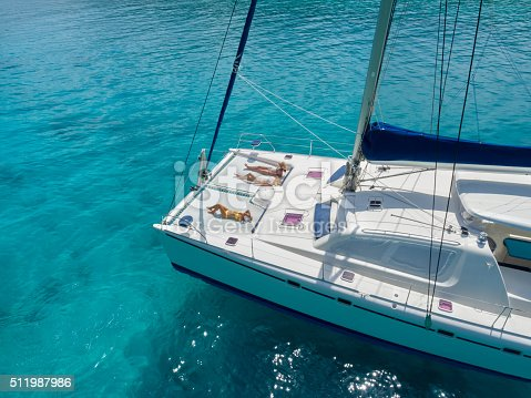 544966382istockphoto Women on trampoline of catamaran anchored in tropical water 511987986