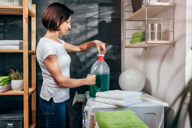 Women opening bottle of liquid detergent Women standing in front of washing machine and opening bottle of liquid detergent laundry detergent stock pictures, royalty-free photos & images