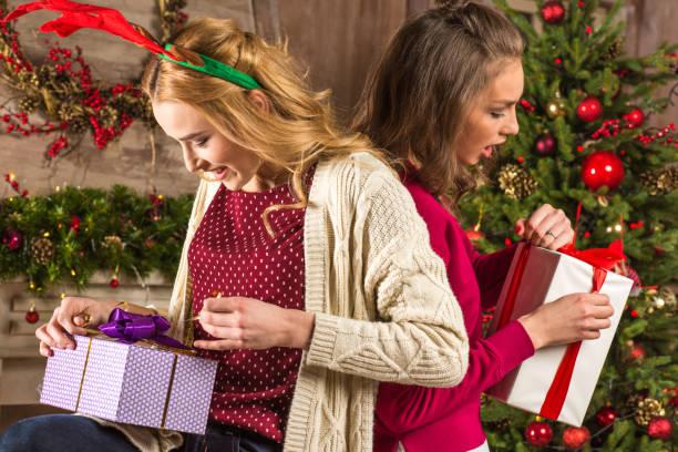 frauen, die weihnachtsgeschenke zu öffnen - besondere geschenke stock-fotos und bilder