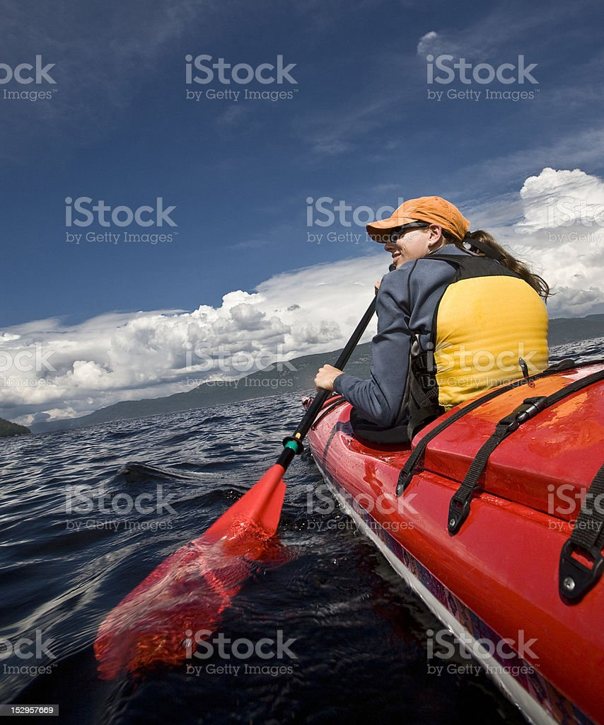 Women paddling in a red kayak stock photo
