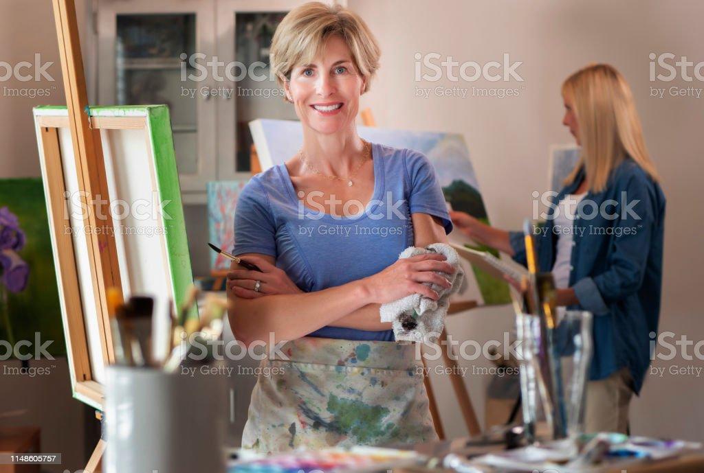 Women painting art on canvas in artist studio.