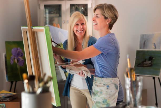 Women painting art on canvas in artist studio. stock photo
