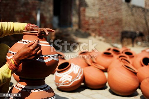 Indian women painting mud pot in traditional style.
