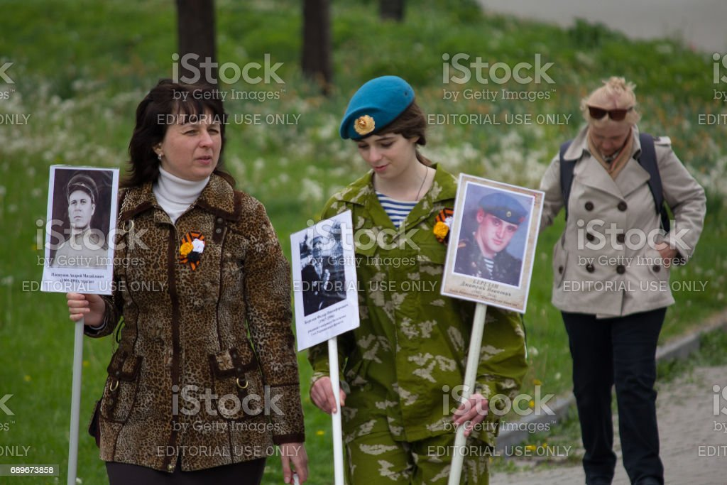 Women participating in procession immortal regiment with portraits stock photo